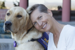 A seated woman is leaning her head against a yellow labrador retriever sitting to her right. Both are looking directly at the camera. The dog is wearing a purple assistance dog vest.