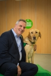 Peter Gorbing is sitting with his arm around a yellow Labrador retriever. The dog is wearing a green assistance dog vest.