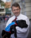 Richard Lord is smiling at the camera while holding a black puppy wearing a blue assistance dog vest.